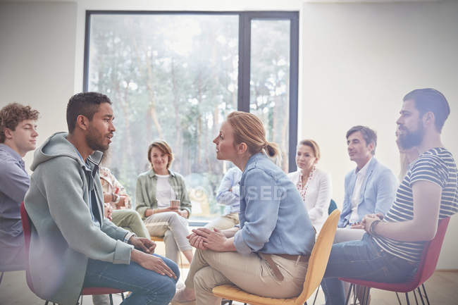 Group watching man and woman talking face to face in group therapy session — Stock Photo