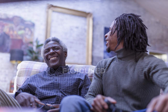 Grandfather and grandson laughing, playing video game on sofa — Stock Photo