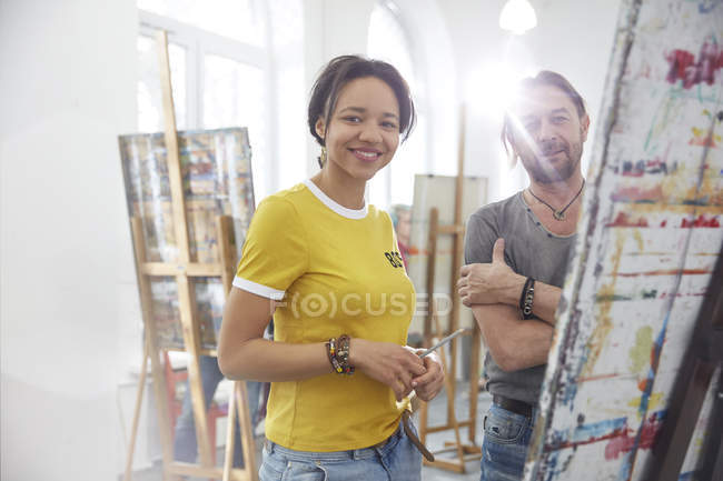 Portrait smiling artists painting at easel in art class studio — Stock Photo