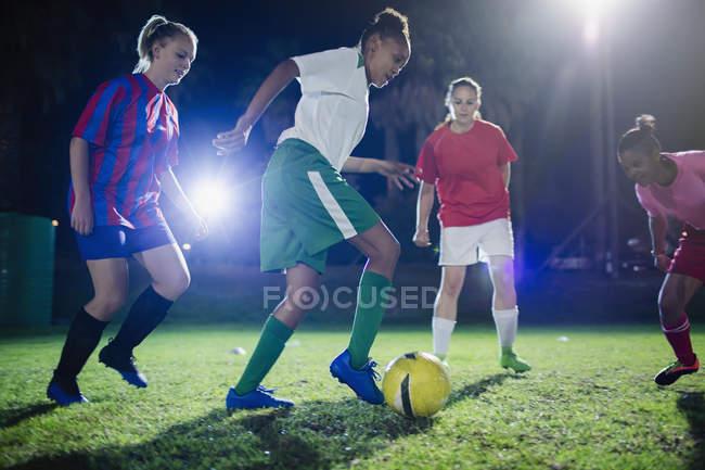 Молода жінка футболістів грали у футбол на полі вночі, ногами м'яч — стокове фото