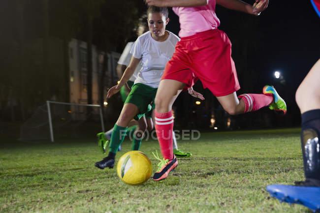 Junge weibliche Fußball-Spieler spielen auf Feld in der Nacht, den Ball — Stockfoto