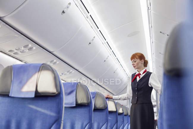 Mujer auxiliar de vuelo en avión vacío - foto de stock