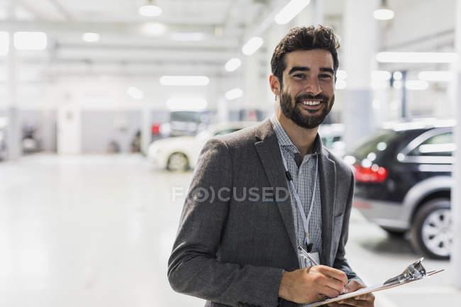 Porträt lächelnd, selbstbewusster Autoverkäufer mit Klemmbrett im Autohaus — Stockfoto