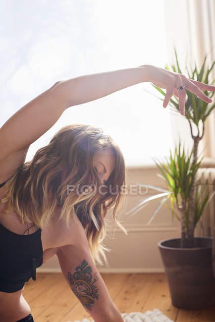 Жінка з тату практикуючих йогу боку органу стрейч — стокове фото