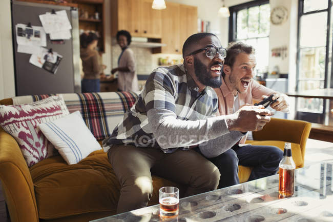 Male friends drinking beer and playing video game in living room — Stock Photo