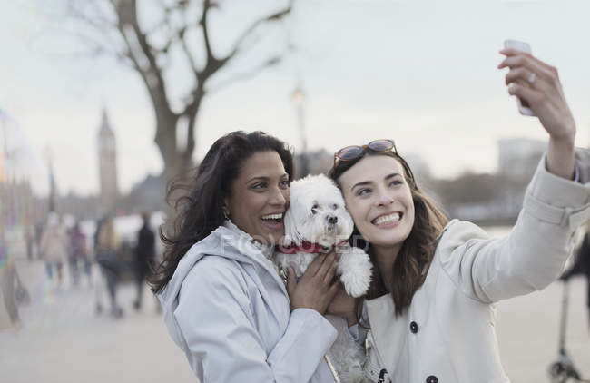 Playful, smiling lesbian couple with white dog taking selfie with camera phone in urban park, London, UK — Stock Photo
