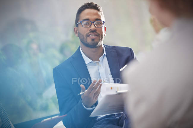 Well dressed black man with clipboard talking in meeting — Stock Photo