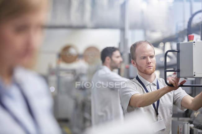 Operaio maschile che utilizza il pannello di controllo delle macchine in fabbrica — Foto stock