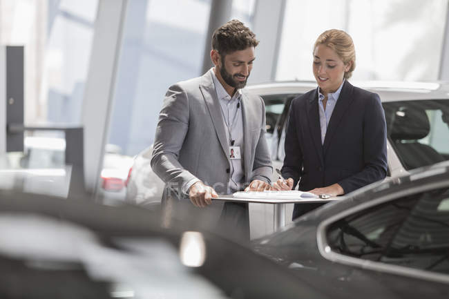 Car salesman and female customer reviewing financial contract paperwork in car dealership showroom — Stock Photo