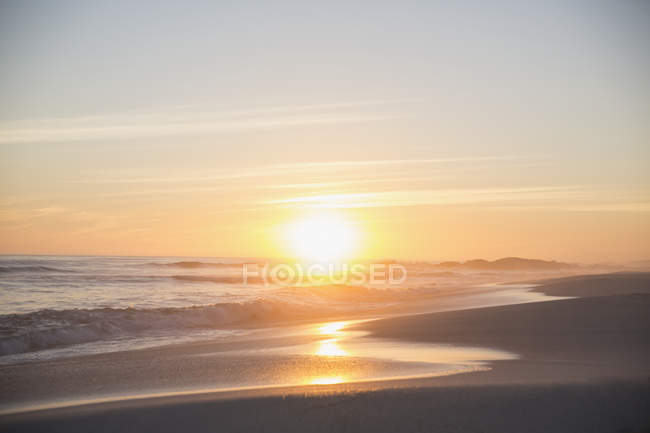 Tranquil sunset view over ocean beach — Stock Photo