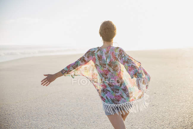Carefree woman walking with arms outstretched on summer beach — Stock Photo