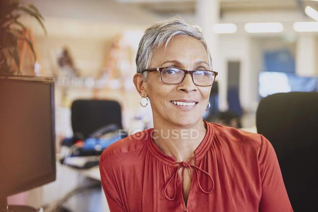 Ritratto donna d'affari sorridente in ufficio moderno — Foto stock