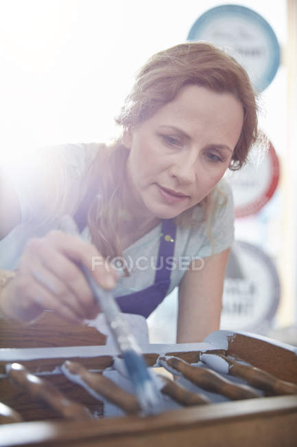Focused female painter painting furniture with blue paint — Stock Photo