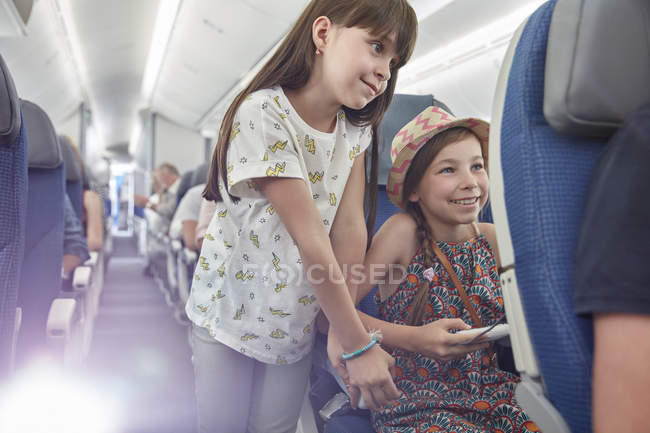 Girl sisters playing video game on airplane — Stock Photo