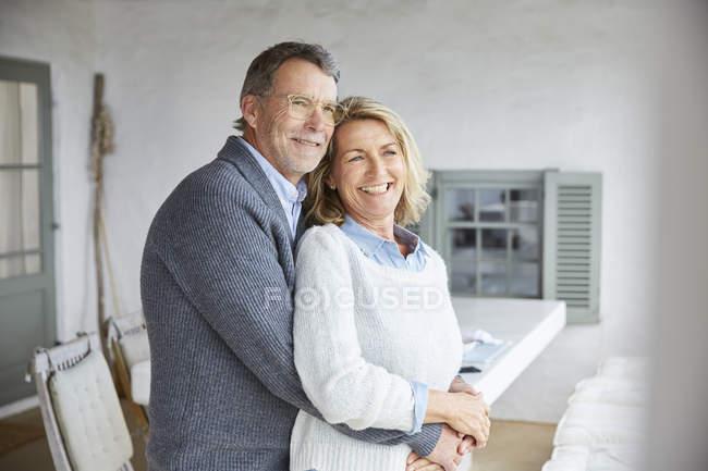 Sonriente pareja cariñoso abrazando en el patio - foto de stock