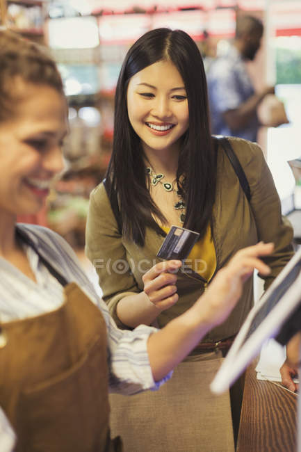 Female cashier helping smiling customer with credit card at grocery store cash register — Stock Photo
