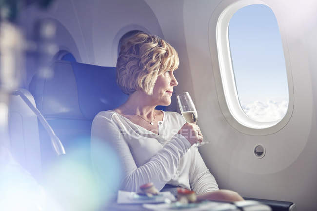 Mature woman drinking champagne, looking out window in first class on airplane — Stock Photo