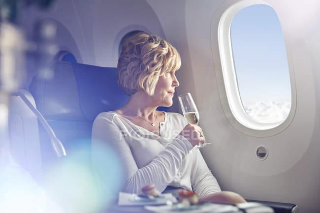 Mulher madura bebendo champanhe, olhando pela janela em primeira classe no avião — Fotografia de Stock