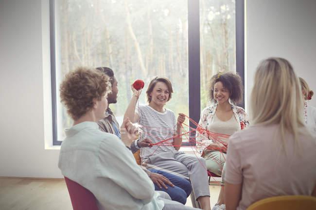 Sesión de terapia de grupo haciendo ejercicio de team building con hilo - foto de stock