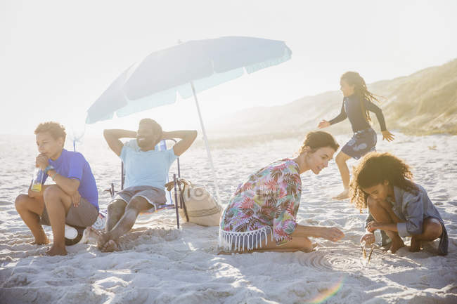 Multi-ethnic family relaxing and playing on sunny summer beach — Stock Photo