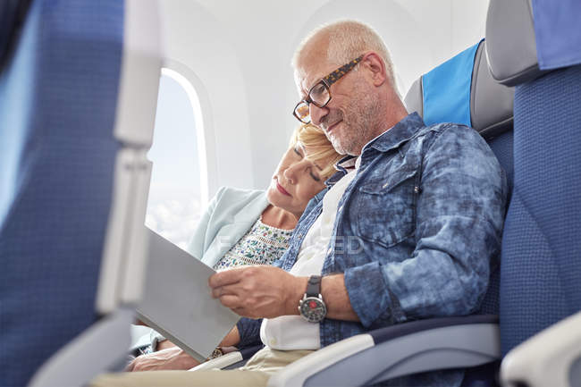 Affectionate mature couple sleeping and reading on airplane — Stock Photo