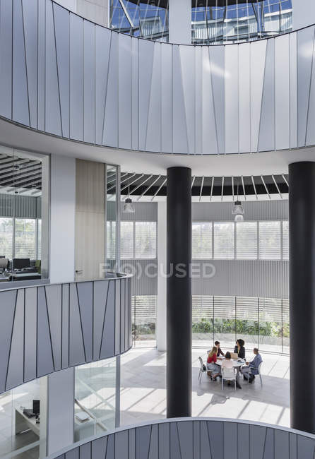 Business people meeting at table in architectural, modern office atrium — Stock Photo