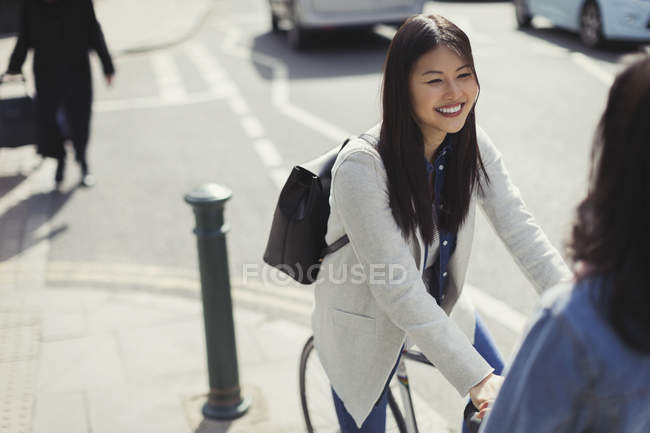 Smiling young woman commuting, riding bicycle on sunny urban sidewalk — Stock Photo