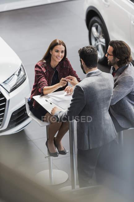 Autoverkäufer übergibt Autoschlüssel an lächelnde Kundin im Autohaus — Stockfoto