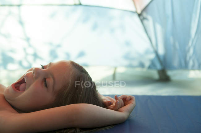 Tired girl yawning, resting inside tent — Stock Photo
