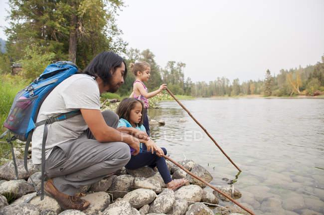 Padre e figlie pesca con bastoni sul lungolago — Foto stock