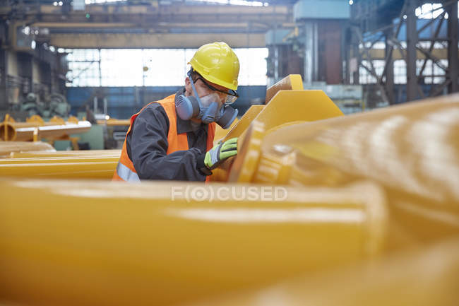 Steel worker wearing protective face mask, examining equipment in steel factory — Stock Photo