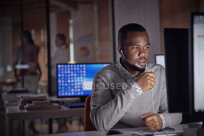 Businessman working late at computer, using hands-free headphones talking on telephone — Stock Photo