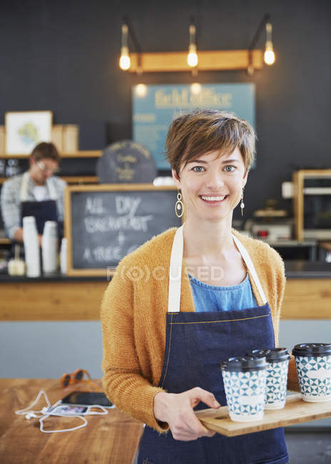 Portrait confident female cafe owner holding tray of coffee cups — Stock Photo