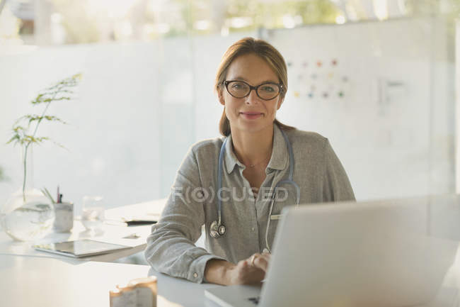 Portrait confident female doctor working at laptop in doctor?s office — Stock Photo