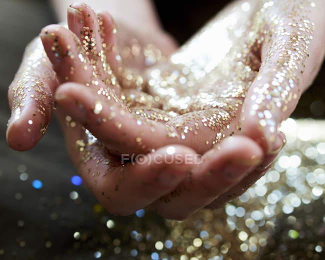 Закрыть вверх руки, купирования Золотой глиттер — стоковое фото