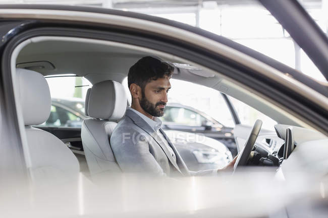Male customer sitting in driver?s seat of new car in car dealership showroom — Stock Photo