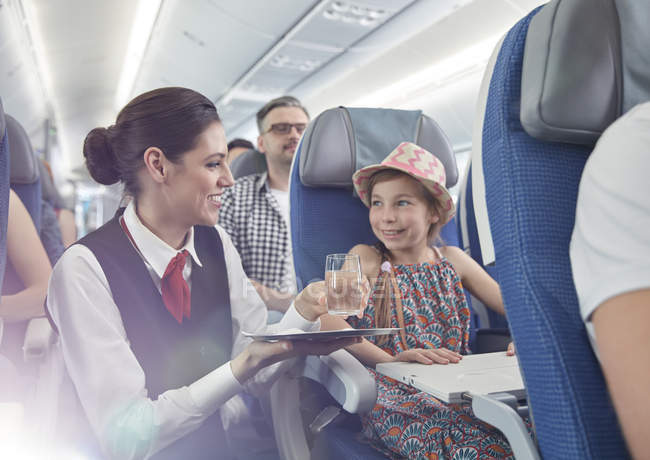 Mujer Asistente de vuelo que sirven agua a niña en avión - foto de stock
