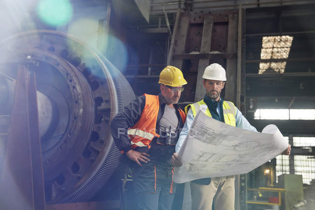 Engineers reviewing blueprints in steel factory — Stock Photo