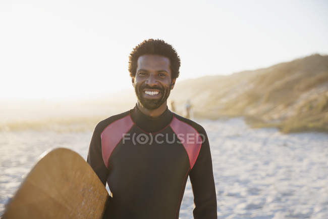 Portrait smiling, confident male surfer with surfboard on sunny summer beach — Stock Photo