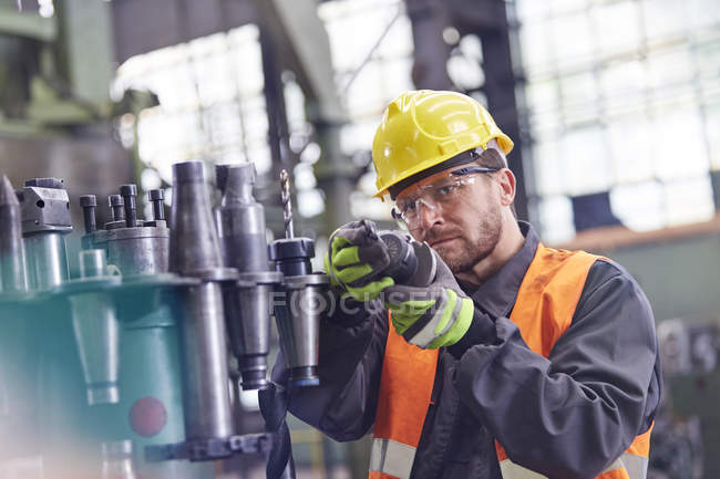 Male worker examining steel parts in factory — Stock Photo