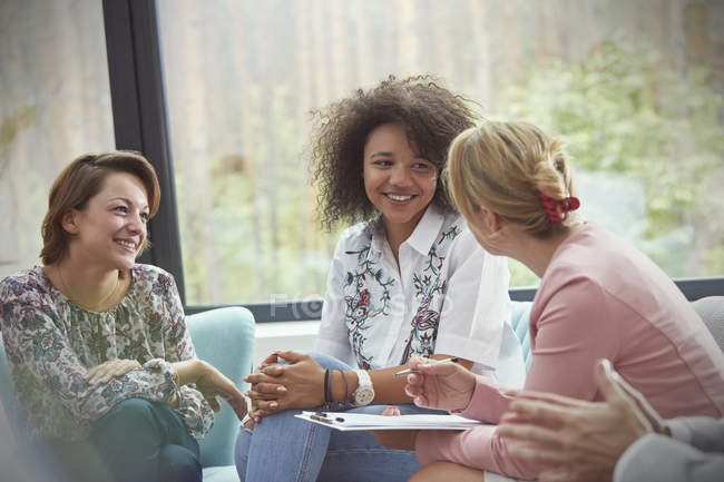Smiling women talking in group therapy session — Stock Photo