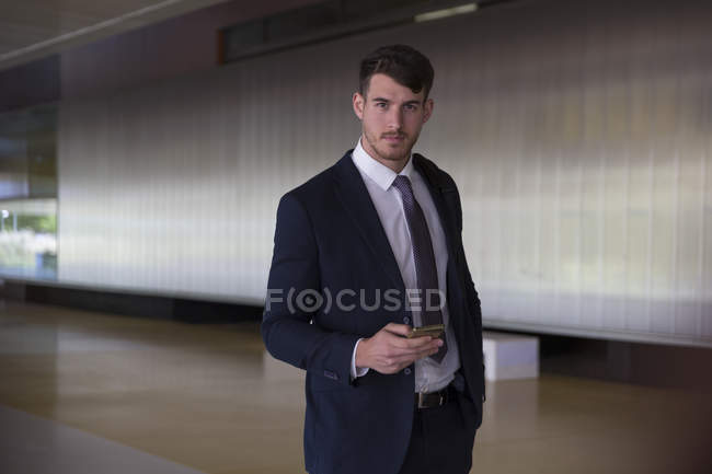 Portrait confident, serious businessman texting with smart phone in office lobby — Stock Photo