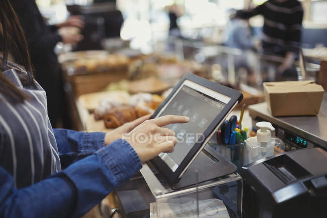Cashier using touch screen cash register in cafe — Stock Photo