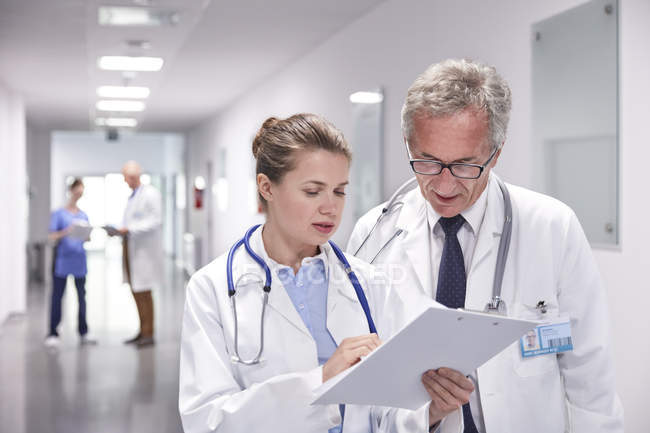 Doctors with clipboard making rounds, talking in hospital corridor — Stock Photo