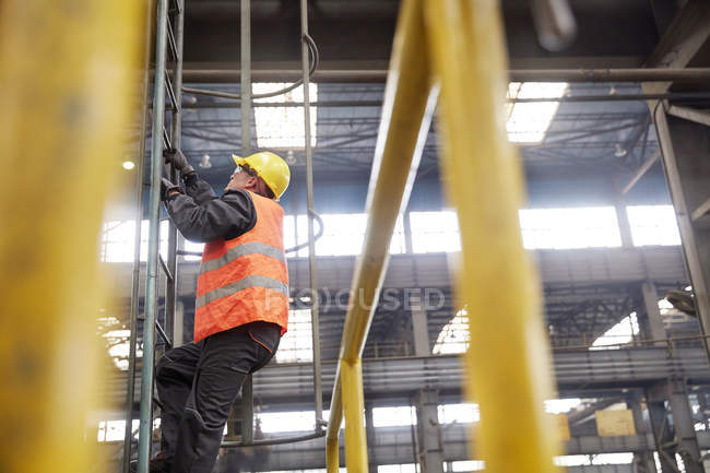 Male worker climbing ladder in factory — Stock Photo