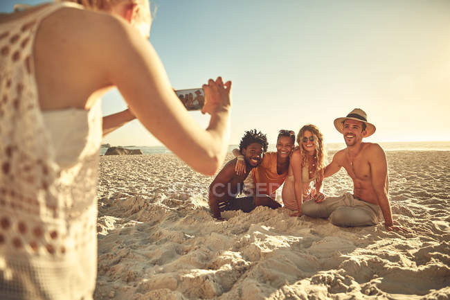 Young woman with camera phone photographing friends on sunny summer beach — Stock Photo