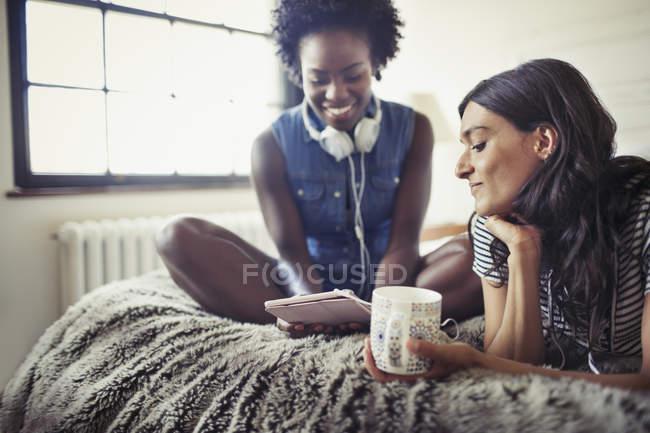 Mulheres com fones de ouvido e café usando tablet digital na cama — Fotografia de Stock