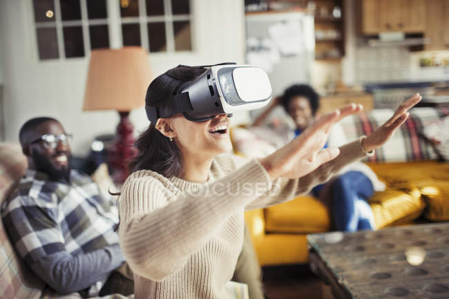 Woman gesturing, using virtual reality simulator glasses in living room — Stock Photo
