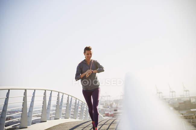 Smiling female runner checking smart watch fitness tracker on sunny urban footbridge — Stock Photo