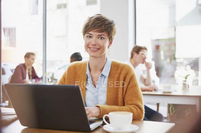 Портрет улыбающейся деловой женщины, пьющей кофе, работающей за ноутбуком в кафе — стоковое фото